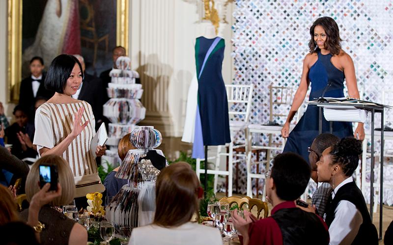 First lady Michelle Obama wears a dress designed by FIT Fashion Design student Natalya Koval at a White House event in 2014.  A dress designed by FIT Fashion Design student Chelsea Chen, left, acknowledges the crowd, while a dress of her design is displayed on the podium besides Mrs. Obama. Associated Press covered the story.