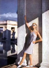 woman with white sunglasses in dress and white shoes leaning against building