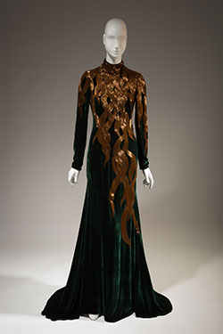 dark green velvet long sleeves evening gown with hand beaded amber-gold bugle beads in a falling hair tresses pattern at upper dress fading to nothing at hem