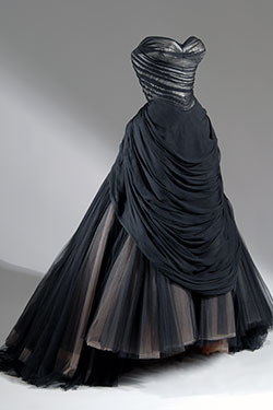 strapless black ballgown with sweeping trained full skirt with layers of black, beige, and brown net gathered into back bustle roll