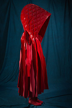 red ensemble with oversized detachable hood and cape with streamer-like panels cut from upper boduce to hem