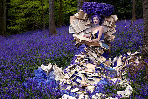 woman in dress covered with pages of books with purple headdress and surrounded by purple flowers