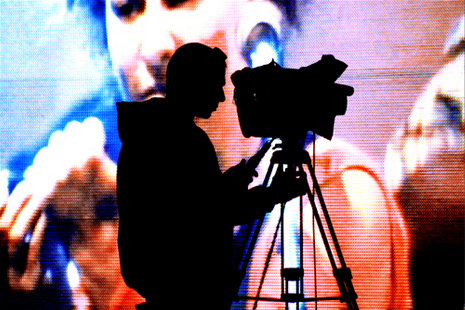 boy with camera in front of film screen