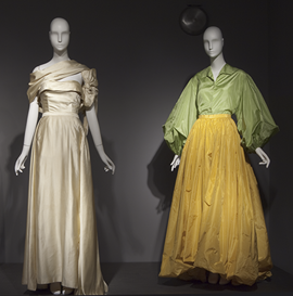 two mannequins: left in ivory gown, right in green top and yellow skirt
