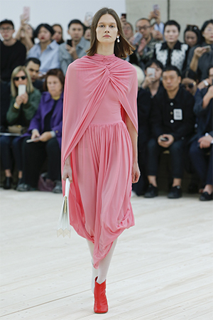 Light pink jersey dress with cape on model on runway