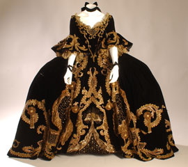 18th-century French inspired dress in black velvet with border of gold metallic lace, applique, sequins, and tassels