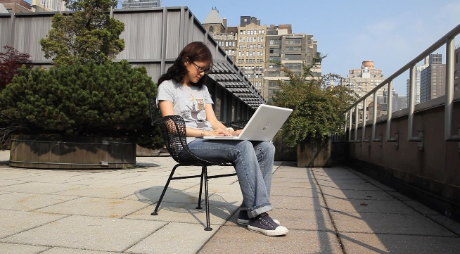 student sitting on the roof working on her laptop