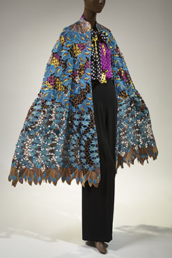 cape in blue and brown hand cut cotton and lace; multicolored polka dot and striped blouse and black pants