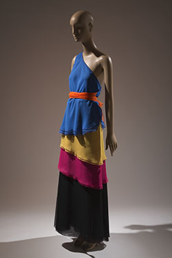 color block one shoulder tiered dress in bright blue, yellow, pink, and black with large orange bow at right side