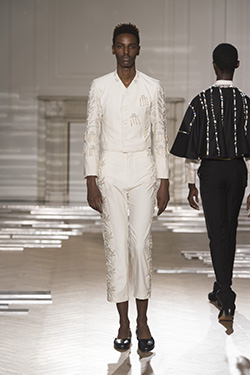runway image of model wearing off-white suit with bead design going down sleeves and legs