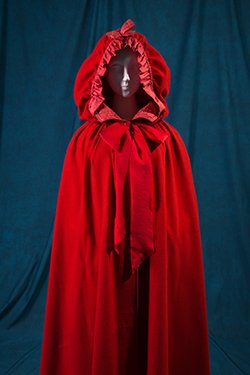 long cape in bright red felted wool with attached hood and buttoned front vest