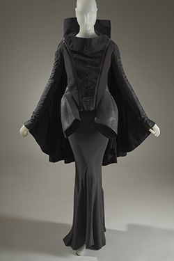 bat wing jacket with silver metal zippers in off-black denim with floor length grey skirt