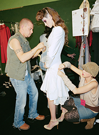 mcqueen assisting dressing a model backstage