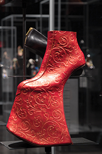 instllation view of red and gold leather shoes with invisible heel