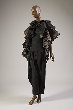 black and metallic pleated tiered cape with black camisole peplum top and tapered pants