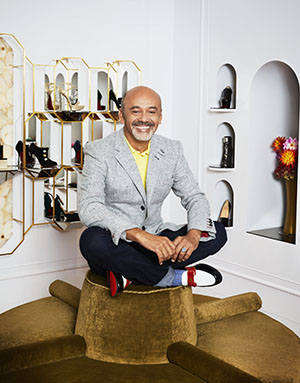 Christian Louboutin sitting on gold chair with shoes in shelves behind him