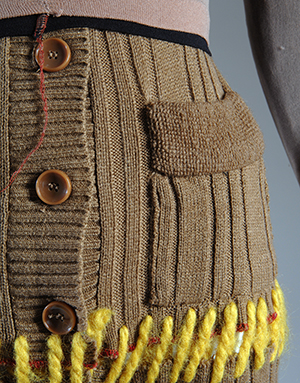 close up of repurposed brown sweaters stitched together with yellow yarn and three brown buttons