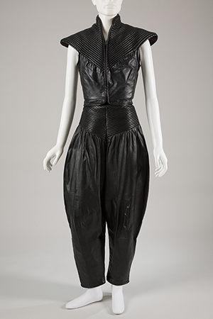 Black leather sleeveless vest with broad trapunto shoulders,high collar and V-yoke. Dressed with leather harem pants with peg leg gathered into trapunto hip yoke.