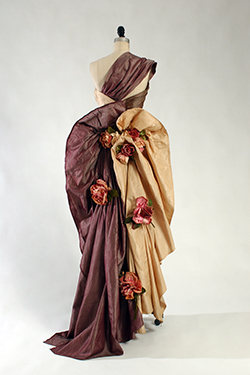 one-shoulder assymetrical evening sheath in three shades of silk shantung, rose-beige, taupe, and lavender with asymmetrically draped skirt with back twist forming bustle and swag and large silk roses scattered on back
