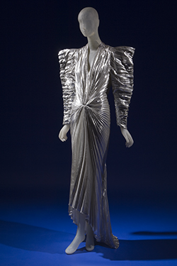 long evening dress in pleated silver metallic lamé with futuristic angular styling wide padded shoulders