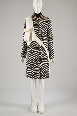 zebra print coat with black turtleneck and skirt, off white cross body bag, gold ball earrings, and white leather sneakers