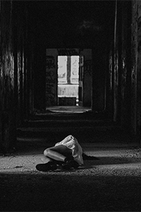 Black and white photo of woman lying on ground in abandoned building