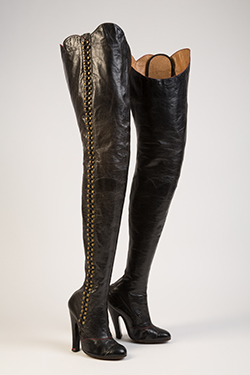 black thigh-high lace up boots with 118 brass hooks at outside leg opening and black laces