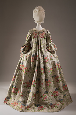Robe à la française of brocaded silk with flower sprays in shades of red, peach, pink, blue, and green and leaves meander pattern on cannele ground