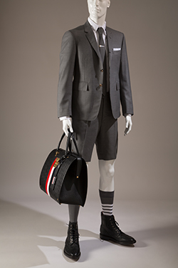 man's ensemble; grey wool short suit, jacket, shorts, tie, white cotton shirt, pocket square, silver tie bar, black leather wingtip boots and grey socks