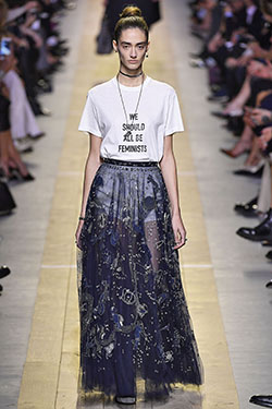 model walking down runway in sheer blue embroidered and embellished skirt and white t-shirt that read 'We Should All Be Feminists'