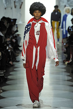 model walking down runway wearing a red jumpsuit with the American flag on sleeves
