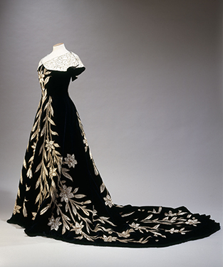 "House of Worth, ""Lily Dress"" evening dress, black velvet with application of ivory silk in the form of lilies, embroidered with pearls and sequins, 1896. © L. Degrâces et Ph. offre/ Galliera/Roger-Viollet."