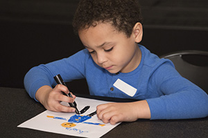 young boy at desk coloring picture