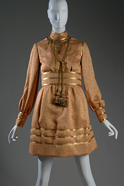 short cocktail dress with gold braid collar, placket, cuffs and hem, and attached brass filigree necklace with pendant tassels and wide belt