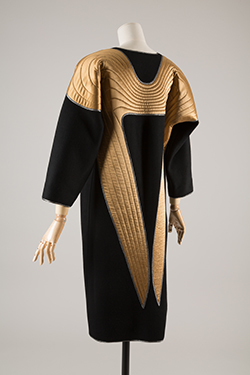 black coat and dress with quilted gold wing motif on shoulders and back