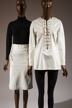 two mannequins: (l)long sleeve black shirt with white leather laced skirt (r) white leather laced tunic