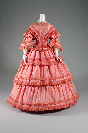 1857 full length pink dress with tiers of fringe-trimmed taffeta, corset bodice and belled sleeves