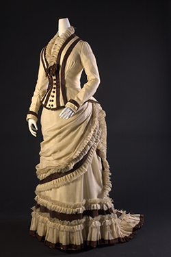 cream and brown dress with bustle, corset bodice and ruffles spiraling down bottom